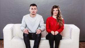 Ung man och kvinna sitter i en soffa och sneglar på varandra
