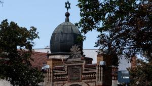 En synagoga. I framgrunden ser en stor port i tegel, i bakgrunden en lökkupol i svart stål. I toppen finns Davidsstjärnan. På sidan om synagogan växer träd.