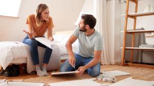 En kvinna grälar med en man som monterar en möbel.