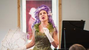 Oopperalaulaj Marie Finne-Bray vihreässä iltapuvussa, violetti peruukki päässä ja päivänvarjo kädessään, taustalla flyygeli, katsojien selkiä kuvan laidoilla.