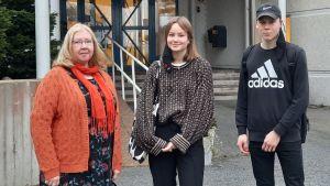 En lärare och två studerande står framför Pedersöre gymnasium.