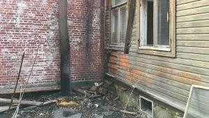 Delar av en vägg i ett trähus har brunnit, bråte på marken.