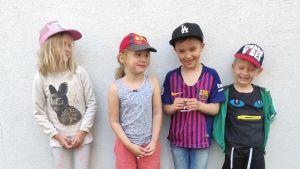 Fyra små barn, två pojkar och två flickor, står framför en vit vägg och ser glada ut.