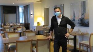En man iklädd munskydd står i en tom, stor restaurang med dukade bord.