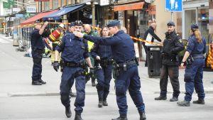 Polisbefäl gestikulerar till kollegor i Stockholm.