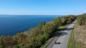 En bild tagen uppifrån luften, med drönare. Till vänster syns blått hav. Till höger två cyklister som kommer cyklande på en landsväg. Träden är gröna och rostbruna. Det börjar bli höst.