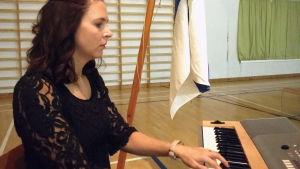 En kvinna sitter vid en elorgel och spelar i en skolas gymnastiksal. Bakom henne finns också Finlands flagga.