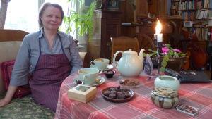 En kvinna sitter vid ett bord fyllt med praliner och chokladkonfekt och kaffekoppar (Med kakaodryck)