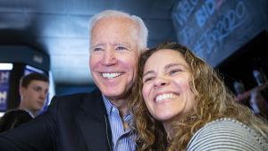 Joe Biden ler stort mot kameran när han poserar med en supporter
