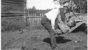 """Två män leker leken """"prova nacken"""", där den ena ska lyfta upp den andra med bara styrkan av sin nacke. Bilden är tagen 1932 i Terjärv."""