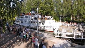 Insjöfartyget M/S Suometar i kanalsluss, flera människor står och tittar på.
