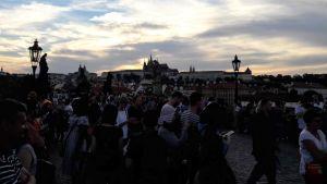 Karlsbron i Prag i skymingen. Massor med människor, i bakgrunden slott