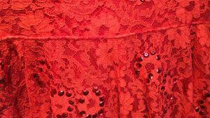 Rött spetstyg med rubinröda paljetter.