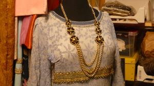 """En klänning i silvergrått med gulddekor och ett tungt halssmycke i """"guld"""" med guldblommor. Teaterdräkt till Lady Marian i pjäsen Robin Hood"""