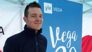 Daniel Eriksson bredvid en Yle Vega 20 år skylt.