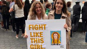 """Caoimhe Craven och Sarah Kelly i New Yorkhåller ett plakat med texten """"Fight like this girl"""" och en tecknad bild på Greta Thunberg."""
