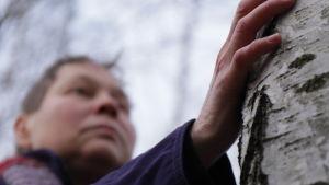 Blind kvinna känner på träd