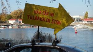 """En skylt på ett biltak där det står """"Här får ni tillbaka er sten"""". I bakgrunden syns en båthamn."""
