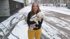 Ung kvinna med hund i famnen.