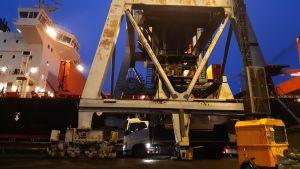 En lastbil står intill ett fartyg, det lastas petrokoks på lastbilen.