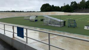 Velodromen i Helsingfors. Betongen är sliten och våt av regn, och i mitten finns en grön gräsmatta gjord för amerikans fotboll.