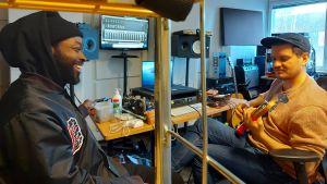 Jesse Markin skrattar, Totte Rautiainen spelar bas i en studio full av musikutrustning och skärmar.