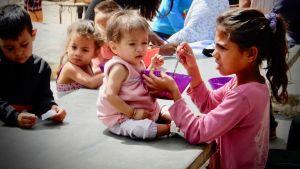 Lapsi ruokkii aliravittua pikkusisartaan Venezuelassa