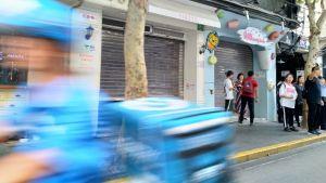 Ohikiitävä verkkokaupan kuljetusskootteri Shanghain katukuvassa
