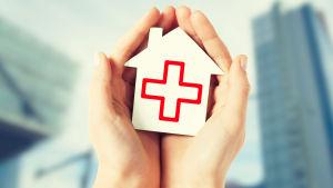 Händer håller i ett hus med ett rött kors på.