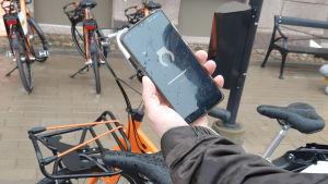 En smarttelefon med en applikation så man kan hyra stadscykel.