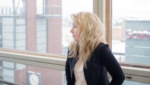 En kvinna som står framför ett fönster.
