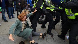 Kvinna drabbar samman med polis i London. Hon faller bakåt på bilden