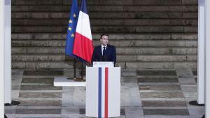 Bild på frankrikes president framför en kista.