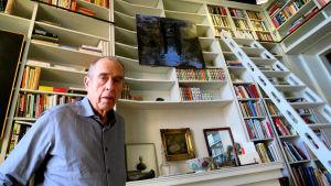 Författaren Jörn Donner står framför hög bokhylla med stege