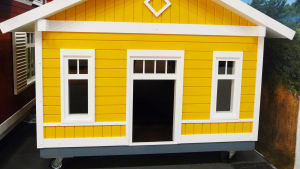 En gul liten byggand (bod) med vita knutar. Står tätt intill ett rött hus.