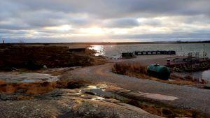 en sandig väg i solnedgången bredvid klippor och hav