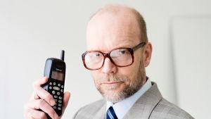 Kari Heiskanen katsoo (roolissaan Kari Kairamo) kameraan kädessään vanha Nokian puhelin.