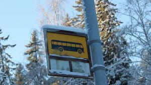 Ett snötäckt trafikmärke för busshållsplats vid en stolpe
