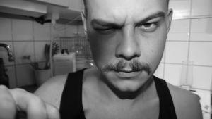 En man iklädd ett svart linne. Han har mustasch och kisar mot kameran. Han står i ett kök.