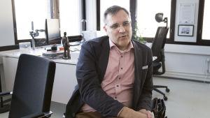 Mikael Pentikäinen istuu toimistossaan.