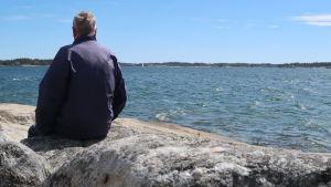 Mies istuu kalliolla katsetta mereen päin