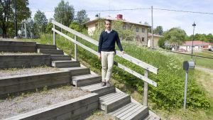 En man iklädd en ljusblå skjorta och en mörkblå tröja. Han är utomhus och han lutar sig mot ett trappräcke. I bakgrunden skymtar en skola och en lekplats.