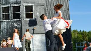 En man lyfter upp en kvinna på en scen i en dans. mannen bär svarta byxor och en skjorta och kvinnan har en vit klänning med rött skärp. De tittar varandra i ögonen. I bakgrunden syns ett högt mörkt hus.
