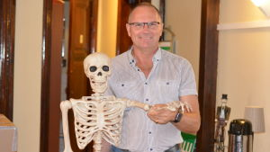 En man som håller i ett skelett.
