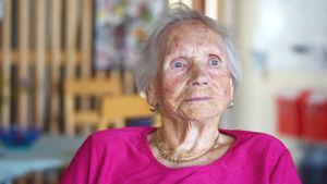 Äldre kvinna med blå ögon klädd i rosa skjorta och med guldsmycke runt halsen.