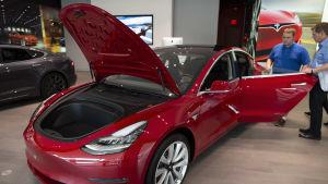 En potentiell köpare bekantar sig med en Tesla Model 3 hos en bilhandlare i Boston den 7 augusti 2018.