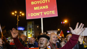 Motståndare till namnbytet firar det låga valdeltagandet framför parlamentsbyggnaden i Skopje.