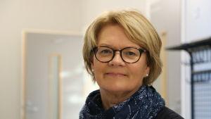 En medelålders kvinna med glasögon och ljust kort hår. Runt halsen har hon en blå halsduk.