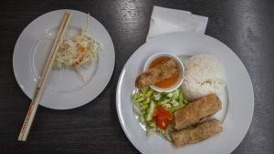 En portion vietnamesiska vårrullar med gurk- och tomatsallad.