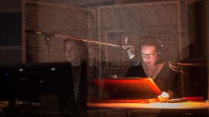Kuvailutulkki Anu Aaltonen äänitysstudiossa. Äänisuunnittelija Tomi Dahlman näkyy äänitarkkaamosta heijastuksen kautta.